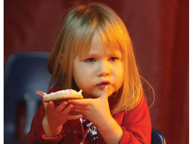 Julina Hoffman, 3 and a half, enjoys a cookie decorated with frosting and sprinkles at the festival.