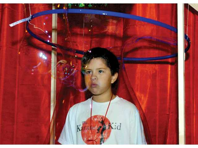 Parker Williams, 10, blows his way out of a bubble tunnel in the Children's Corner during the Festival of Trees.