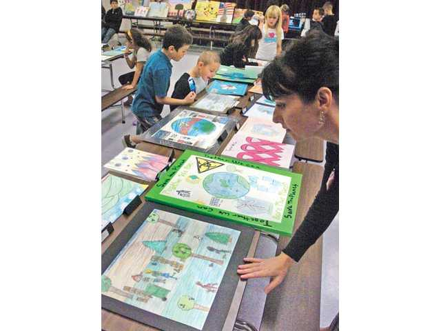 Parent Stacy Gibby, right, examines some of the hundreds of pieces of artwork, literature and photographs Tuesday, which were created at Plum Canyon Elementary School.