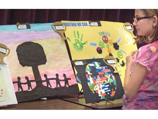 "Katie Mularky, 9, looks at the award-winning entries created by fellow students in grades kindergarten through sixth at Plum Canyon Elementary School in Saugus on Tuesday. The display was part of a program themed ""Together We Can,"" which was hosted by the school's parent-teacher association."