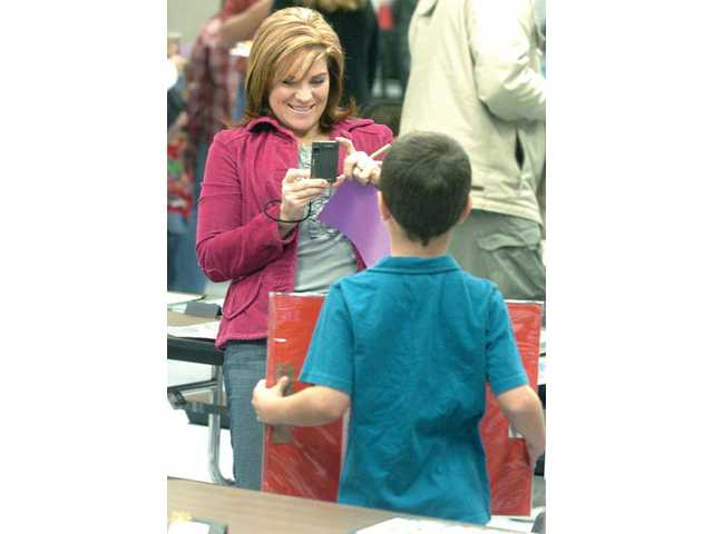 Mother Glenna Panarisi takes a photo of her 6-year-old son Carson's creation at the school's PTA-hosted Arts Recognition and Achievement program, which was held Tuesday.