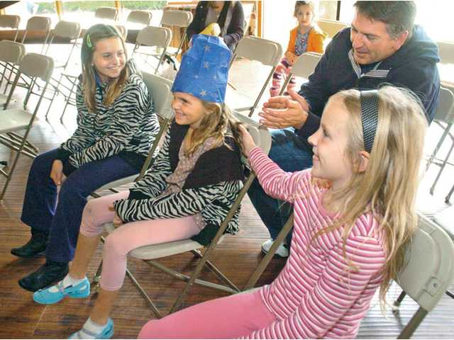 John Smith, rear, applauds as his daughters, from left, Lilly, 9, Emily and Sydney, both 7, enjoy an illusion by magician Lincoln Bond during his 24-hour magic show Sunday in Valencia.