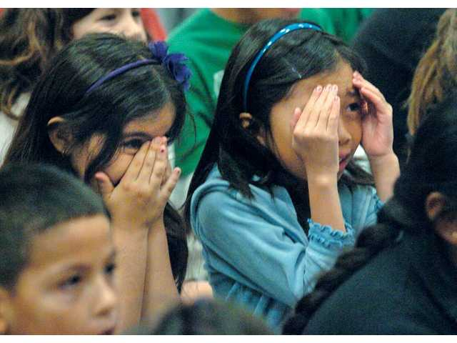 "Third-graders Sydney Lopez, left, and Josephine Jose cover their eyes as they watch Russel Edge of Faustwork Mask Theatre play a scary character. Edge performed a act titled ""The Mask Messenger"" at Rio Vista Elementary School in Canyon Country on Wednesday."