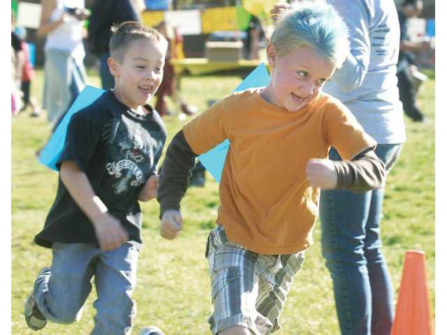 First-graders Nolan Whiteman, left, and Michael Pote, with his hair dyed blue for Crazy Hair Day, run for another lap. The students raised money for their school with each lap they completed.
