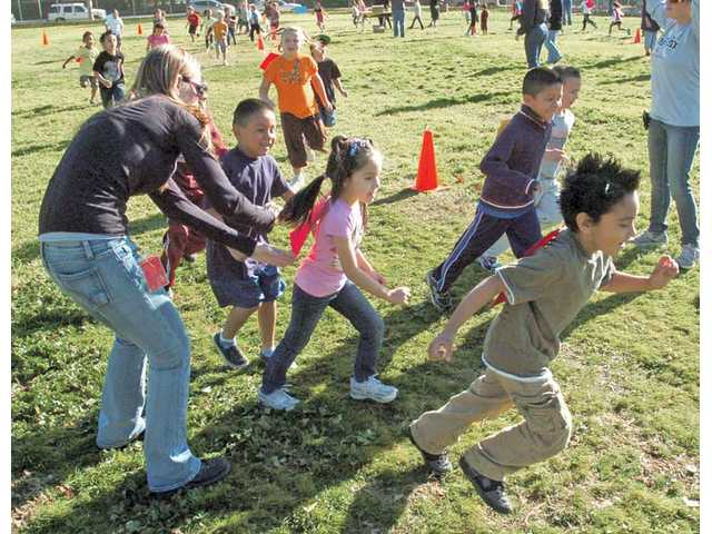 Parent volunteer Melissa Simmons, left, tags the first-graders as they complete another lap of a jog-a-thon fundraiser at Santa Clarita Elementary School in Saugus on Thursday.