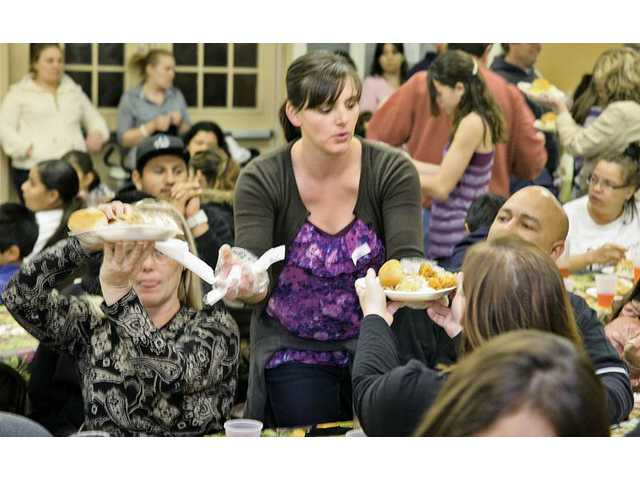Real Life Church of Valencia volunteer Lindsey Leitelt serves Thanksgiving-style dinners to some of the hundreds of local residents who attended the Val Verde Community Center event in Val Verde on Tuesday night.