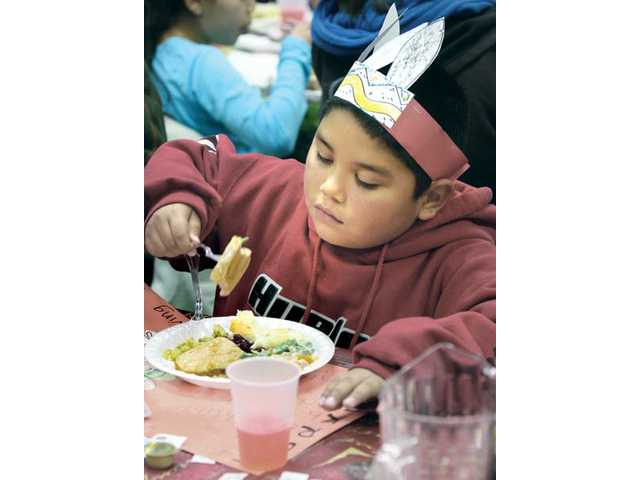 Sebastian Lopez, 7, of Val Verde, sports a turkey feather hat as he enjoys his dinner.