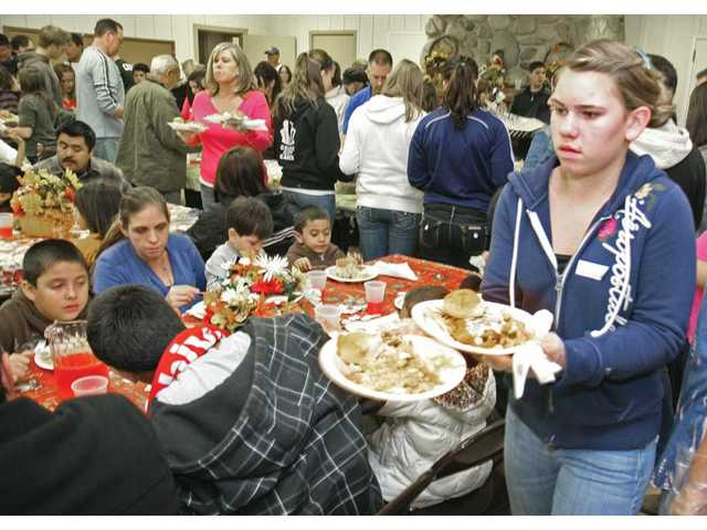 Real Life Church of Valencia volunteer Kayla O'Shea, 12, right, helps serve the dinners. The event recognized the contribution of more than a dozen members of the community.
