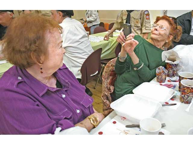Pat Gold, left, poses as her friend Linda Ryan takes a photo with her phone camera during a Thanksgiving Day feast at the Santa Clarita Valley Senior Center on Thursday.
