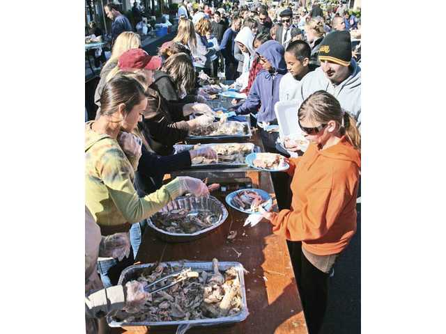 Hundreds gather for a free Thanksgiving Day meal organized by Roger Hasper and his wife, Shannon, behind Hasper's bicycle-repair shop, the Newhall Bicycle Company, in Newhall on Thursday.