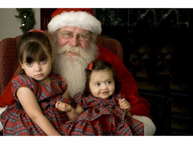 Mary, left, and Amanda Suarez chat with Santa last year. Children are once again invited to visit Santa at all of the Dilbeck 14 offices.