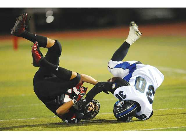 Santa Clarita Christian's Chris Fechtelkotter, left, gets pulled down as Excelsior Education's Joe Harrison fumbles the ball on Friday at Canyon High School in the semifinals of the CIF-Southern Section Division I 8-man playoffs.