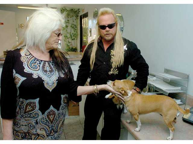 """Kevin """"K-Nine"""" Gilger poses alongside an image of Duane """"Dog"""" Chapman from the A&E television series """"Dog the Bounty Hunter"""" at Gilger's home in Castaic."""