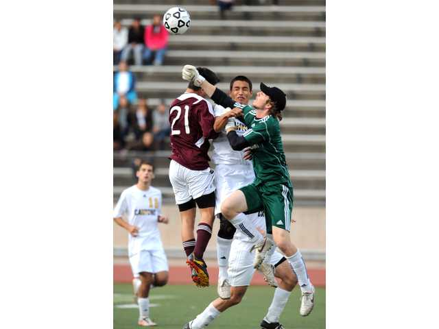Cougars goalkeeper Alex Burkevics, right, punches the ball away as teammate Jose Reyes and Mt. SAC's George Pantoja (21) jump for it during Sunday's state championship game.