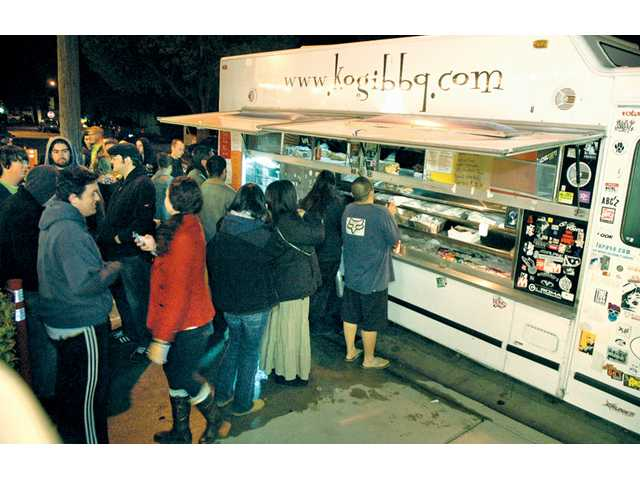 Local residents line up to order some Korean-Mexican fusion food from the Kogi BBQ truck on Chestnut Street in Newhall on Wednesday.