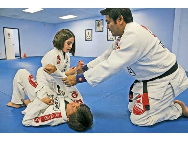 Mia and Dominic are taught jiu-jitsu techniques by Gracie Barra senior instructor Paolo Pacana in the Little Champs 2 class, which is open to students age 7 to 13 and takes place Tuesday and Thursday nights at the studio.