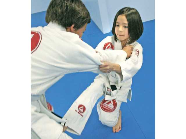 "Mia Bartolovich, 10, practices a takedown jiu-jitsu move on Dominic Vizcarra, 12, at Gracie Barra Jiu-Jitsu Studio in Saugus. Bartolovich started taking classes six weeks ago after being bullied by a boy at school, and says she ""loves it."""