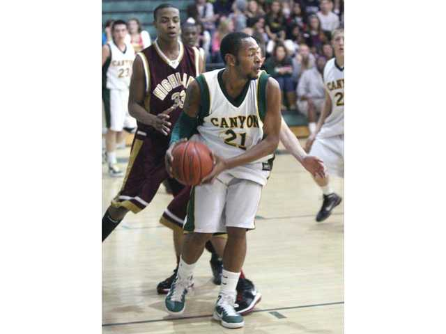 Canyon's Darnel Haggerty (21) looks to pass the ball Friday as Highland's Aaron Jones (33) defends.