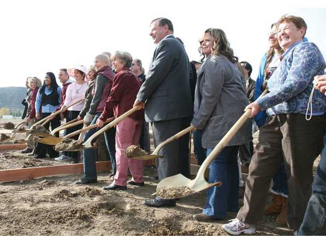From right to left, starting third from right, Councilman Bob Keller, Mayor Pro-tem Marsha McLean and Santa Clarita Mayor Laurene Weste pose for photos as they turn the dirt at the groundbreaking ceremony for the Community Garden of Santa Clarita at Central Park in Saugus on Friday.