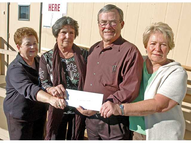 From left, Sue Ryan, Sally Coss, Tim Davis, executive director of the Santa Clarita Valley Emergency Winter Shelter, and Nancy Spicer pose at the shelter Tuesday. The women, part of the Our Lady of Perpetual Help Teabags, presented Davis with a $1,300 check for the shelter.