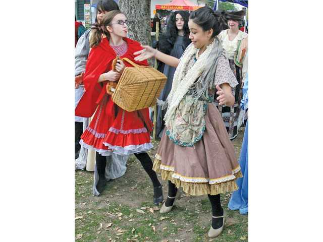 "Emily Rieck, left, as Little Red Riding Hood, sticks out her tongue at Erika Nagai, who plays the The Baker's Wife, as they argue over Red's basket as the Placerita Junior High School drama club performs a scene from the play ""Into the Woods, Jr.""  at Santa Clarita's Literacy and Arts Festival held at Newhall Park in Newhall on Saturday"