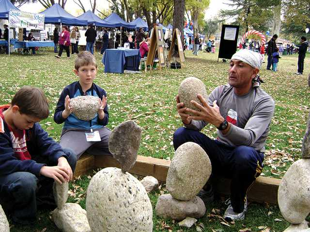 Fidel Garcia, right, of Sequoia Charter School in Santa Clarita, shows students the art of rock balancing during the Litaracy and Arts Festival, which took place on Dec. 4. The festival aimed to spark a passion for reading among local youth.
