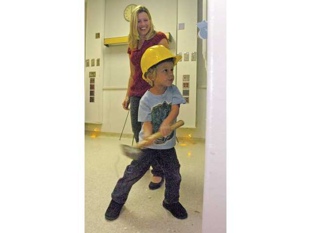 Rowan Smyth, 4, takes a sledgehammer to a wall inside the Newhall Memorial building as his mother, Lena, looks on.