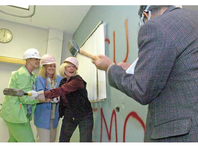 Nurses Jan Berry, left, and Cathy Butler, center, join Sally McGann, director of women's services, in smashing a wall with a sledgehammer inside Henry Mayo Newhall Memorial Hospital's old intensive care unit on Tuesday. At far right is pediatrician Krishan Vashistha, also participating in starting the demolition of the building. A wall-busting celebration was held in preparation of the hospital's new 11-bed neonatal intensive care unit, which is set to open in 2011.
