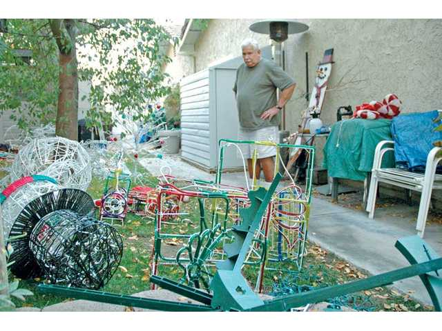 Robert Greenquist surveys Christmas decorations Monday that were strewn across the lawn of his Saugus home by vandals. In light of the incident, his neighbors have helped pitch in to replace the damaged holiday lawn adornments.