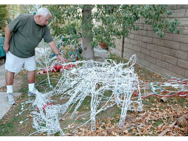 Saugus resident Robet Greenquist begins to clean up Christmas decorations in his yard. After a group of vandals tore down his family's old decorations Sunday night, Greenquist's wife, Patty, debated the effort of putting new ones back up for fear they'd be torn down again.