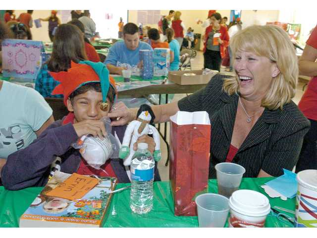 Lori Nazar, right, shares a laugh with Ervin Pancardo, 15, as he holds some of the new toys he got from Santa during the party.