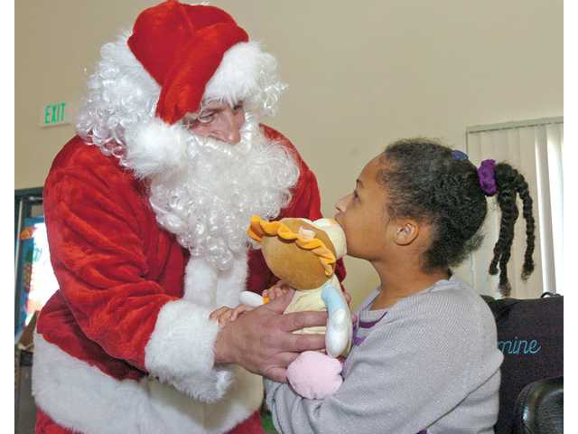 Jasmine Gardere, 17, right, gets a new toy from Santa at the holiday party.