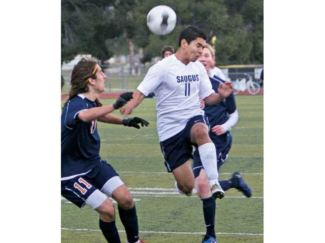 Saugus' Victor De Dios (11) heads the ball past Chaminade defender Nick Uzunyan, left, as Eagle Jaime Bent looks on Wednesday at Saugus High. The game ended in a 2-2 draw.