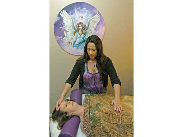 (Above) Reiki master Joan Darlene performs a chakra clearing, which she says are popular with clients of all ages and professions. (Below)