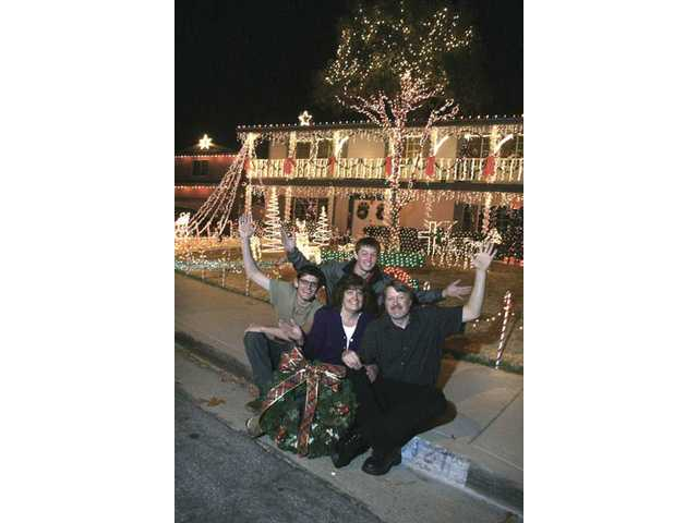 The Maddux family, from left, Joshua, Linda and Jim, with Brandon in the back (Kyle not shown). The Maddux family home at 19121 Dalton St. in Newhall won our Grand Champion award because of its fantastic arrangement of thousands of lights, flashing in perfect synchronization to music.
