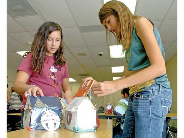 Leslie Alvarez, left, and Darby Laplant, both 13, put the finishing touches on miniature houses made from old holiday-greeting cards at Sierra Vista Junior High School in Canyon Country on Dec. 10. Seventh- and eighth-grade students filled the houses with small gifts to distribute to local families in need.