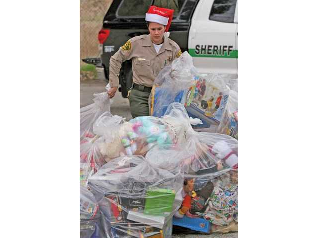 Los Angeles County Sheriff's Department Deputy Regina Yost stacks bags with some of the toys due for pickup by the Santa Clarita Valley Food Pantry from a Pitchess Detention Center storage unit in Castaic on Thursday. The toys will be given to needy families in the Santa Clarita area for the holidays.