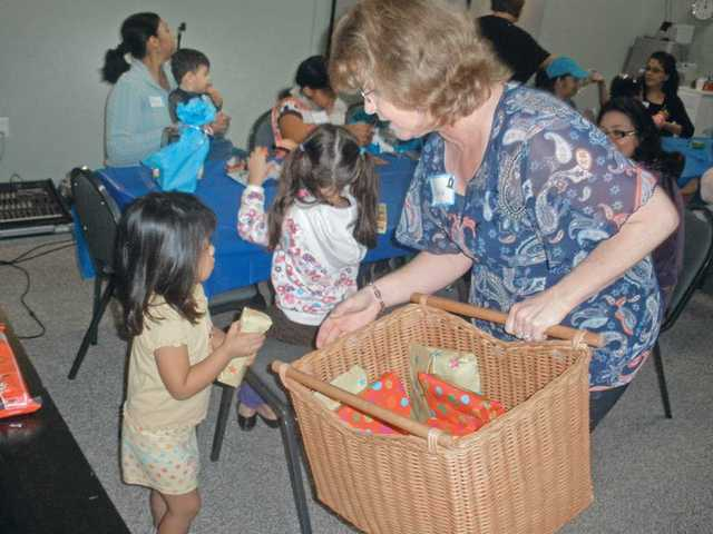 Darla Schackart of Every Road Covenant Church hands out gifts to children as part of the locally-based church's recent outreach project for Single Mothers Outreach. The outreach is part of the church's focus to reach out to the community by creating programs for those in need. The church recently found a new space for its weekly Sunday services at Santa Clarita Tutors.