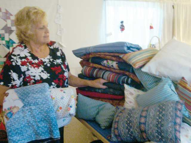 Yvonne Penny, a community service volunteer, stands near the result of a drive by the Santa Clarita Valley Quilt Guild members to make and donate quilts to the homeless served by the charity Under the Bridges.