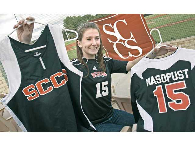 Santa Clarita Christian School senior Joanna Masopust displays her volleyball jersey in her right hand and softball jersey in the left while wearing her soccer jersey. Masopust has played all three sports throughout high school, but she started playing soccer since she was 5 years old.