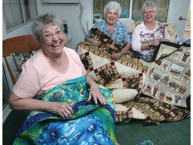 Old Remnants quilting group members, from left, Ginger Grafues, Beverly Van Cleave and Pat Palmer display their quilted works at Grafues' home in Santa Clarita on Thursday. Old Remnants has been meeting six hours once a month for more than a decade.