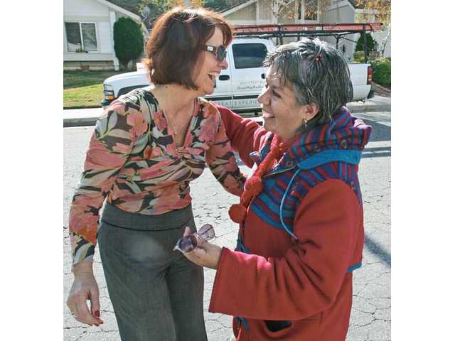 DaAnne Smith of Single Mothers Outreach and Ruth Tofighi-Mendoza embrace outside Tofighi-Mendoza's Saugus home. Tofighi-Mendoza, a client of the nonprofit, was the recipient of a brand new roof from Great Way Roofing.