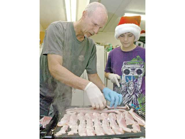 Jack Worth, left, and Vince Schiro, 12, fry bacon as part of the hot meal handed out to the shelter's clients on Christmas Day.