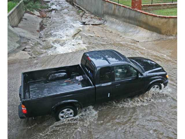 A truck passes through the rushing water that crosses Quigley Canyon Road near Placeritos Boulevard as heavy rains fall in Santa Clarita on Monday. The rains continued through Wednesday, capping the end of nearly a week's worth of storms