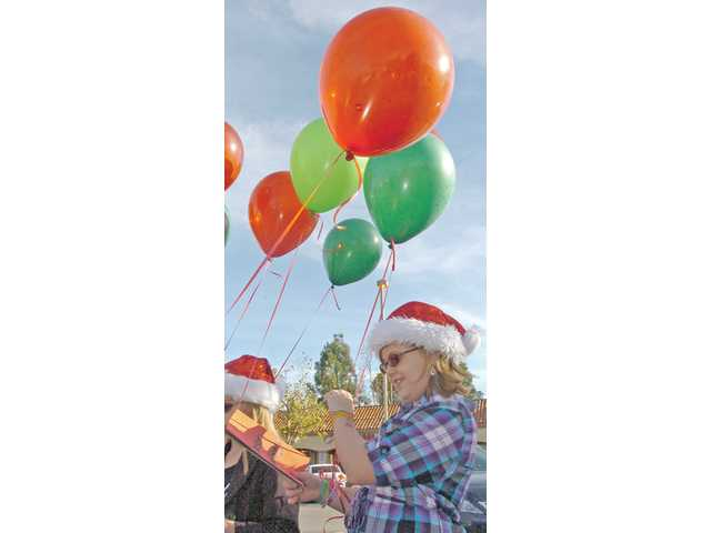 Chloe Bratlien, 9, carries balloons and Christmas cards with a group of about 50 other people preparing to visit Pacific Senior Living in Newhall on Friday. Local families and friends spread holiday cheer and spent time with the seniors who will spend the holiday away from their own families.