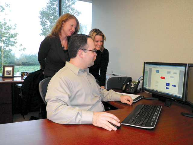 Owner Brian Cuda, front, with Conceptinet staff Nicole Celentano, left, and Cherise Cuda discussing options for a client's website in a recent photo. Conceptinet, a Web-design and website-marketing firm, is based in Santa Clarita.