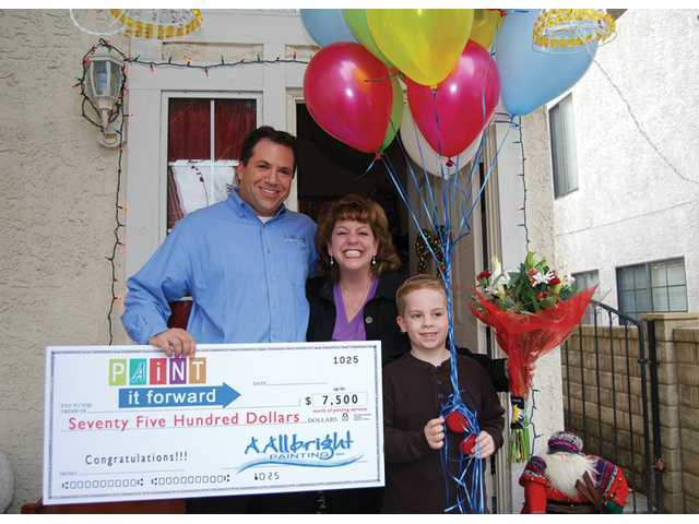 Joshua Abramson, president of Valencia's A. Allbright Painting, presents Keri Ross and her son Joshua, 7, of Saugus, with the sixth annual Paint It Forward prize on Dec. 16. The prize is awarded each year to a family or organization in need. Ross, a recent widow, needed an exterior paint job on her home to meet homeowners association requirements.