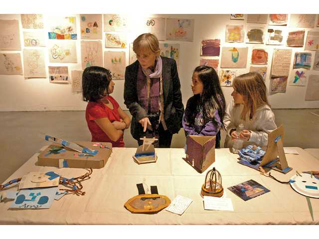 From left, Vanessa Basilio, Darcy Hubler, associate dean of the School of Art at the California Institute of Arts; Isaura Cruz, 8; and Natasha Tobler, 8; discuss the works being showcased in a gallery on the campus on a recent Thursday night. CalArts hosted a reception to showcase the work of Newhall Elementary School students in the Art Pilots program, led by CalArts students and administrators.
