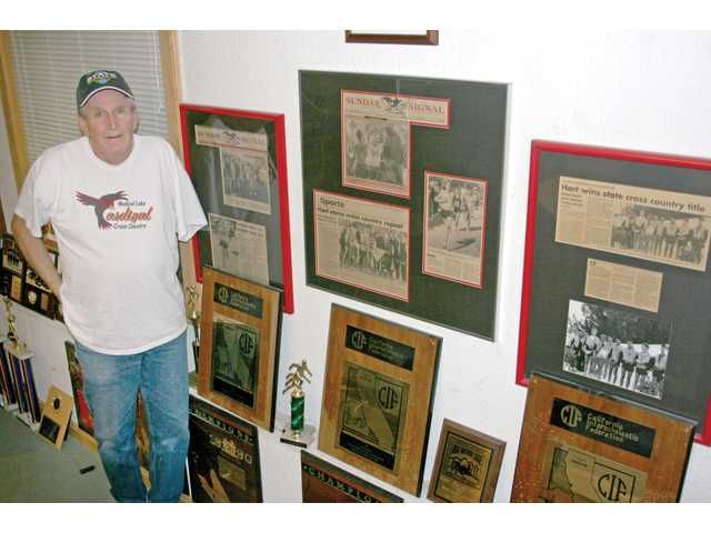 Former Hart High cross country head coach Gene Blankenship stands next to newspaper clippings and CIF plaques at his home in Spokane, Wash. The memorabilia commemorates the three state titles he won while coaching the Hart boys in the early 1990s.