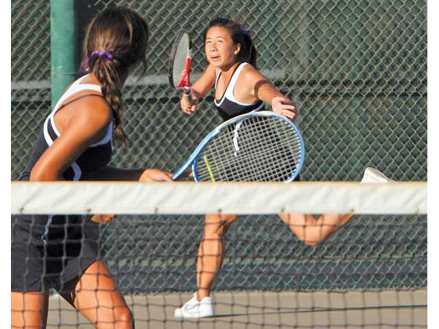 Valencia's Kirstie Kwock (back) chases down a ball as her doubles partner Nicole Zammit watches during a match last season. The Vikings' girls tennis program has won nine straight Foothill League titles, and other programs at the school have also been dominant.
